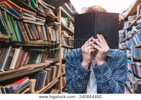 Student Stands In A Cozy, Old, Public Bulletin And Holds The Book In Front Of Him. The Young Man Clo