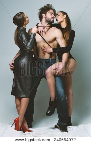 Women In Sexy Bodysuits Hug Bearded Macho. Desire And Lust Concept. Man And Pretty Girls With Seduct