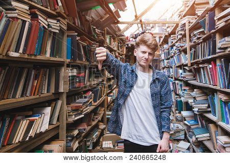 Young Man Stands In A Public Library And Shows A Finger Down. Dislike Library And Books. Student In