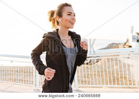 Attractive young sports woman running outdoors on the street listening music with earphones.