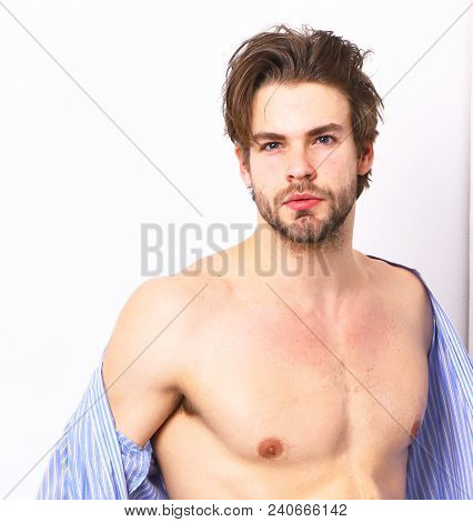 Fit guy with sexy body in home or bath clothes. Masculinity, spa and morning concept. Man with beard in blue dressing gown on white background. Macho in bathrobe with strong chest. poster