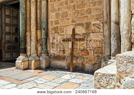 Big wooden cross lean against stone wall of the Church of the Holy Sepulchre in Old City of Jerusalem, Israel.