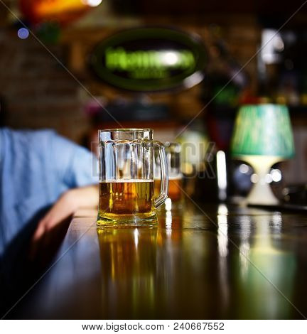 Glass Of Light Beer On Wooden Bar Counter. Man Sits Behind Glass Of Light Beer. Service And Alcohol