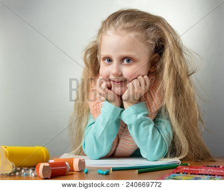 Little Girl Sits At Table With Warm Scarf Around Her Neck, Near Inhaler And Medicine