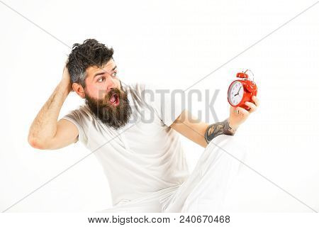 Hipster With Beard And Mustache Overslept. Man With Shocked Face Sits, Holds Alarm Clock. Man Needs