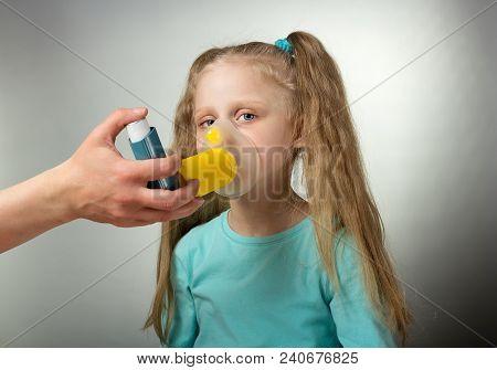 Sick Child Inhales Medicine Through Mask On Gray Background