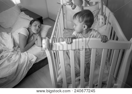 Black And White Portrait Of Tired Mother Falling Asleep Nex Tto Sleepless Baby Boy