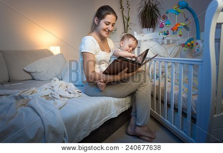 Beautiful Woman In Pajamas Holding Her Baby Baby On Lap And Reading Book At Night