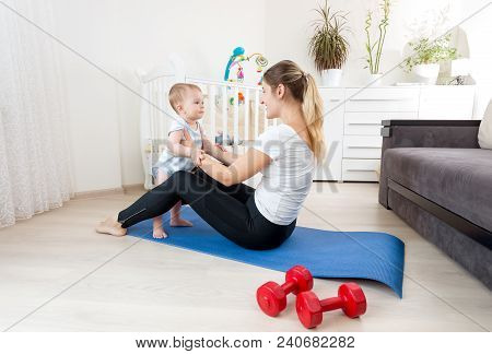 Young Woman Practising Fitness On Yoga Mat With Her Baby Boy