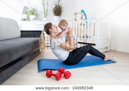 Beautiful Woman Practising Yoga At Home With Her Toddler Son