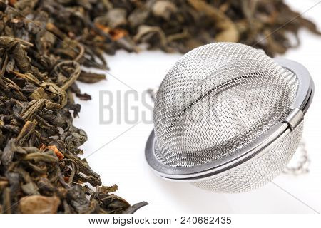 Tea Strainer On A Chain, With A Mixture Of Dry Green Large-leaf Tea With Soursop, Isolated On A Whit