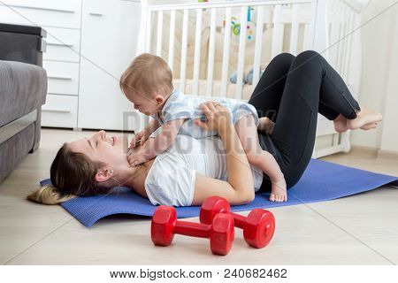 Happy Laughing Woman With Baby Exercising On Floor At Home