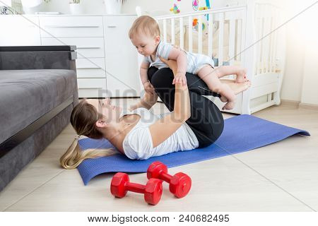 Smiling Woman Lying On Fitness Mat And Holding Her 9 Months Old Baby Boy
