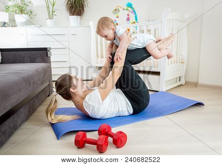 Young Woman In Leggings Exercising On Floor At Home With Her Cute Baby Boy