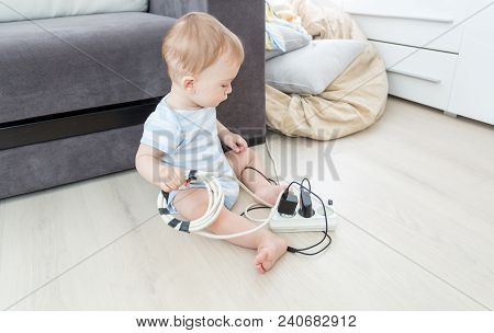 Unatteded Little Baby Playing With Electric Power Cables. Child In Dangerous Situation