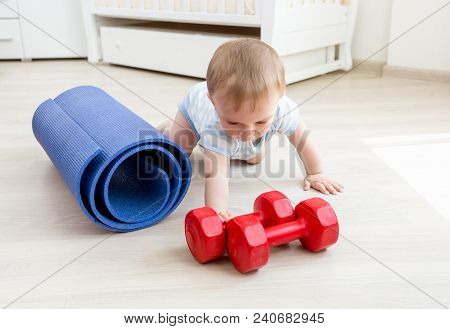 Portrait Of Active Baby Boy Crawling On Floor Towards Yoga Mat And Red Dumbbells. Concept Of Childre