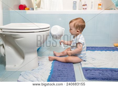 9 Months Old Baby Sitting In Bathroom And Looking On Toilet