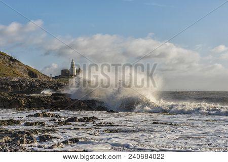 Landscape Image Of Mumbles Lighthouse With Waves Crashing Against The Rocks
