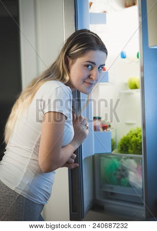 Portrait Of Hungry Woman Sneaking In Refrigerator At Night