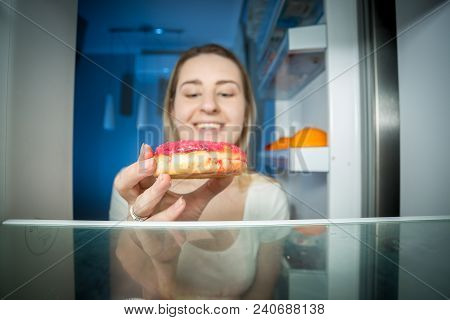 Closeup Photo Of Hungry Young Woman Taking High-caloric Donut From Refrigerator At Night. Concept Of