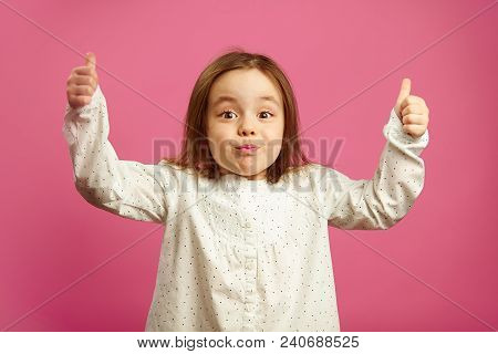 Surprised Little Girl With Raised Hands, Shows Thumbs Up, Has A Stunned Face, Expresses Surprise And