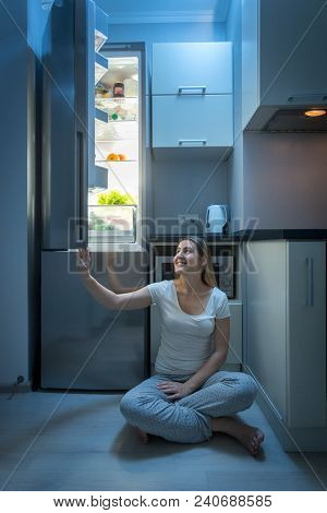 Young Woman Sitting On Kitchen Floor At Night And Opening Refrigerator Door