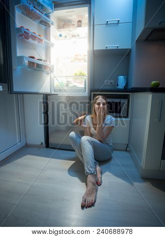 Hungry Woman Sitting On Kitchen Floor At Night And Holding Pizza