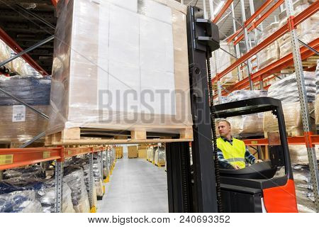 wholesale, logistic, shipment and people concept - loader operating forklift and loading boxes at warehouse
