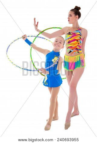 Young Woman And Little Girl Doing Gymnastics With Hoops Isolated On White Background