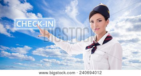 Online Check-in Concept - Stewardess In Uniform Pointing At Check-in Button Over Blue Sky Background