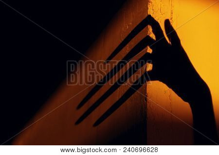 Strange Shadow On The Wall.Terrible Shadow. Abstract Background. Black Shadow Of A Big Hand On The Wall. Silhouette Of A Hand On The Wall. Nightmares. Scary Dreams. poster