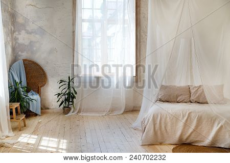 A Cozy Bedroom In Pastel Colors With A Wooden Floor, A Large Four-poster Bed, A Green Flower In A Fl