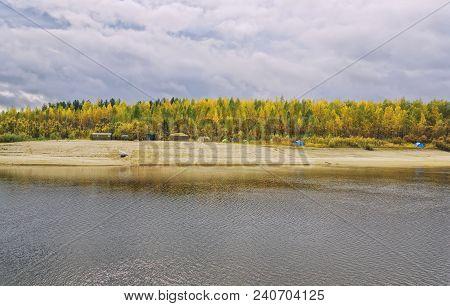 Autumn, Siberia. Multicolored Foliage On Trees. Large Tented Camp On The Bank Of The Taiga River