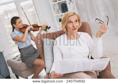 Need To Think. Concentrated Girl Sitting On The Background While Playing The Violin