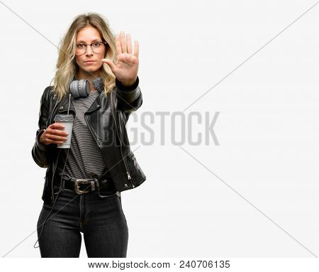 Young student woman with headphones annoyed with bad attitude making stop sign with hand, saying no, expressing security, defense or restriction, maybe pushing