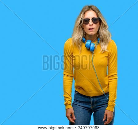 Young beautiful woman with headphones scared in shock, expressing panic and fear