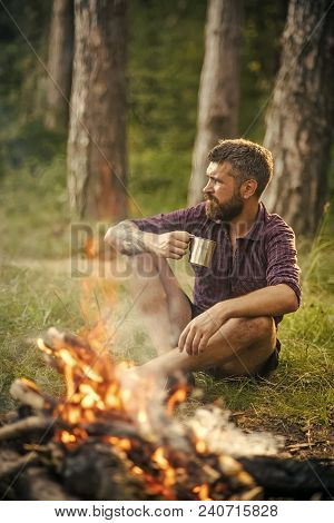Man Traveler Drink Tea At Campfire Flame. Camping, Hiking, Lifestyle. Summer Vacation Concept. Hipst