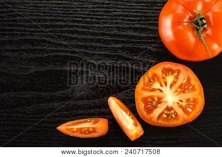 Red Tomato Collection Isolated On Black Wood Background Top View One Whole One Section Half And Two