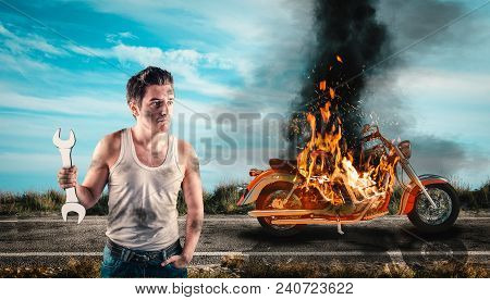 Helpless Man Holding A Wrench With His Motorcycle On Fire In The Background. Needs Help To Repair Th