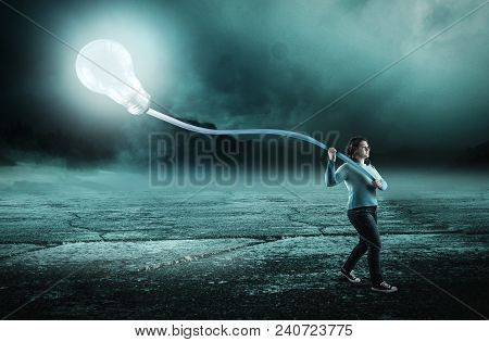 Woman Walk At Night And Carry A Lightbulb. The Concept Of Keep On With An Idea All The Way.