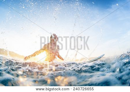 Surfer haves fun and makes water splashes being on line up during sunrise surf session.