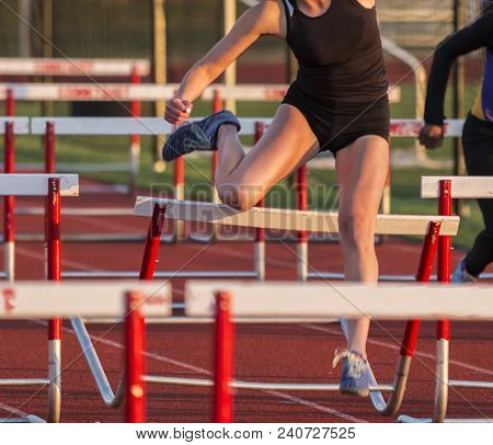 A High School Girls Hits Her Knee On A Hurdle While She Is Running A Race At A Track And Field Compe