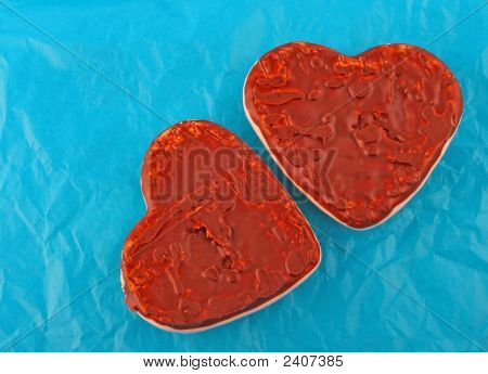 Two Chocolate Hearts Over Blue Paper