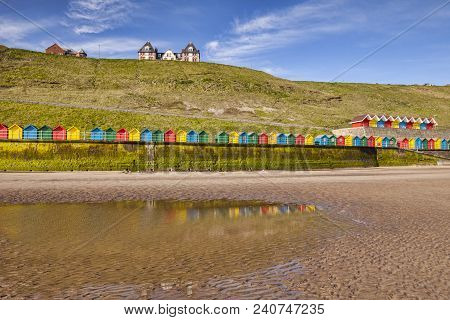 Beach Huts Lining The Promenade And Reflecting In A Pool At North Beach, Whitby, North Yorkshire, En