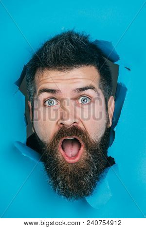Bearded Man Peeking From Ripped Paper Hole. Surprised Or Shocked Man With Beard And Mustache Looking