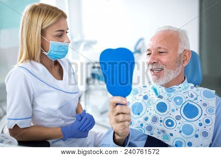 Young Female Dentist And Satisfied Patient