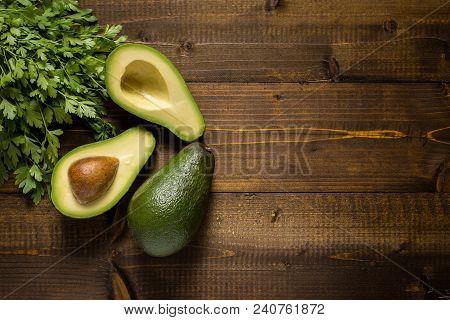 Avocado On Dark Wood Background. Healthy Food Concept.