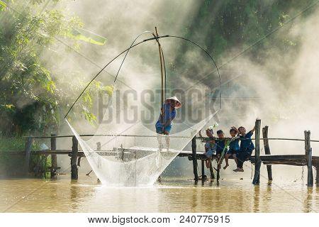Sakon Nakhon, Thailand - July 31, 2016: Rural Man Fishing By Fishing Net While Group Of Rural Childr