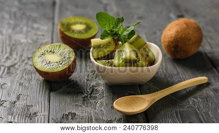 Kiwi Salad And Mint And Kiwi Fruit On A Wooden Table. Tropical Vegetarian Dish.