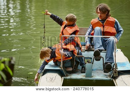 Father And His Two Sons Are Sailing On The Pedal Catamaran Along The River. Everybody Has Life Jacke